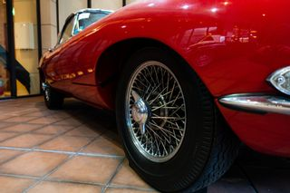 Close up of the wheel of a Red Jaguar E-Type
